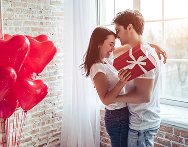 couple embracing with girl holding red gift 8 challenges long distance relationships face and how to overcome them from Milena Nguyen healthista e1523270813345